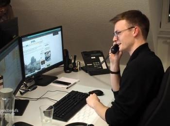 Mitarbeiter vorm Bildschirm mit Telefon