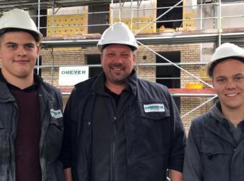 Mitarbeiter vor einem Gerüst auf einer Baustelle