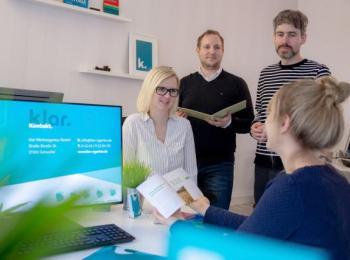 Team bei der Besprechung mit Monitor an der Seite