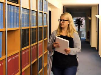 Mitarbeiterin an einer Bücherwand mit Gesetzestexten
