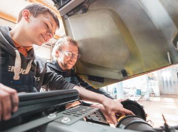 Azubi und Mitarbeiter arbeiten an einem Fahrzeug